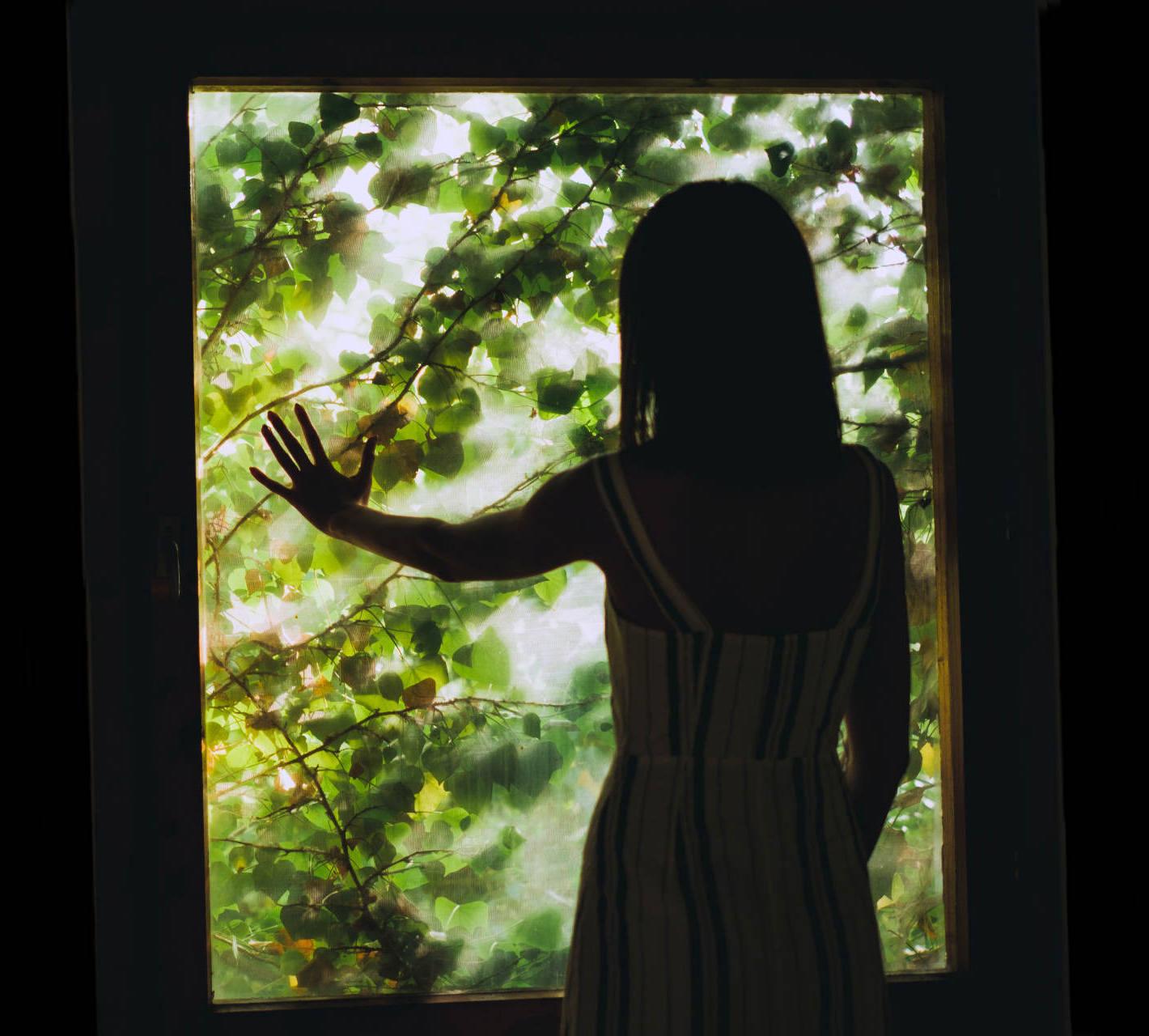 Teenage girl at a garden window